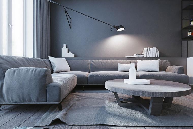 Arredo salotto con un divano angolare grigio e tavolino rotondo, decora la tua casa
