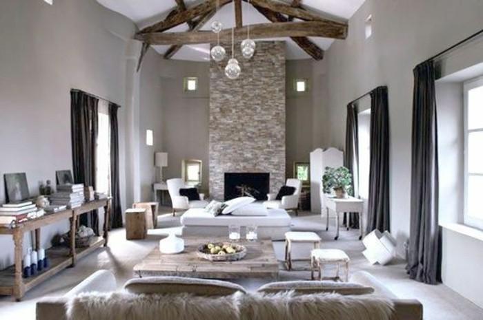 Salotto con mobili in legno, color tortora abbinato al bianco, soffitto rustico con travi in legno