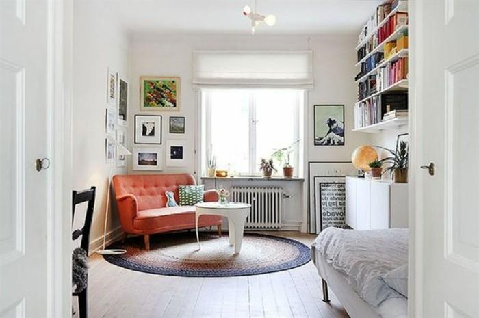 un'idea per arredare piccoli appartamenti con pareti bianchi, un divano vintage arancione e una libreria sospesa
