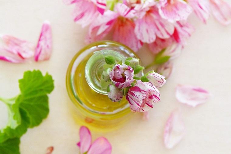 Olio eterico di fiori, cura del corpo, foglie di menta verdi, bottiglia di vetro piccola con olio all'interno