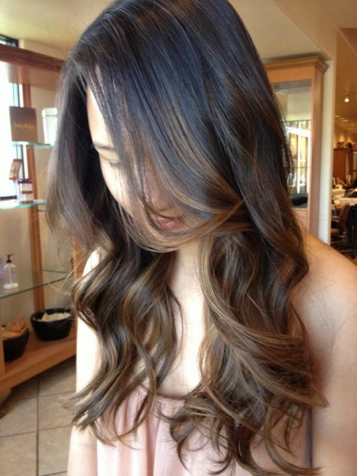 una ragazza con i capelli lunghi scalati con dei balayage caramello