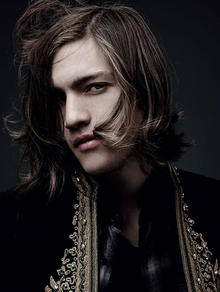 Ragazzo con capelli lunghi di colore castano, abbigliamento elegante con giacca