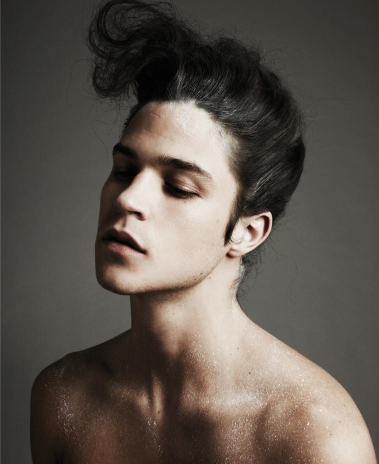 Uomini bellissimi, capelli lunghi colore nero, acconciatura pompadour, corpo ricoperto di sabbia