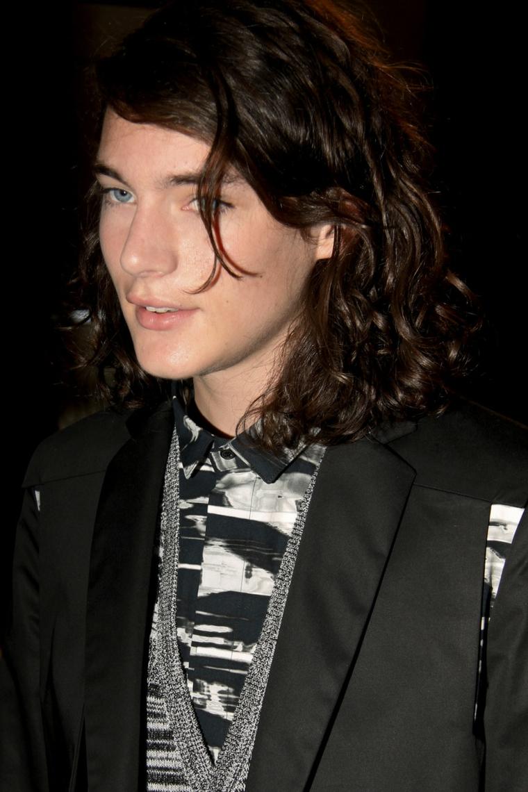 Tagli di capelli ragazzo, colore castano lunghi e ricci, abbigliamento elegante bianco e nero