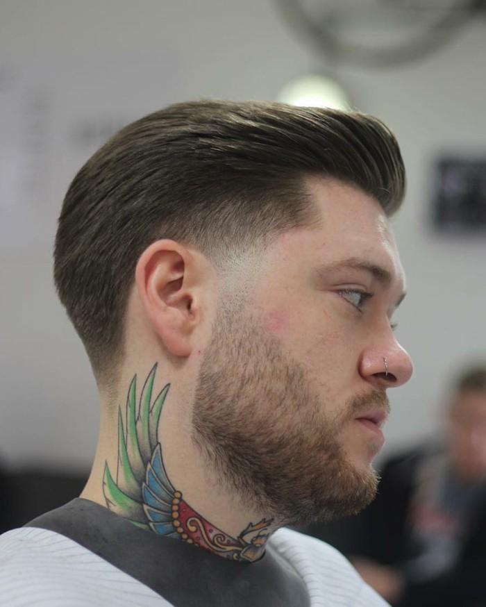 idea per tagli maschili corti con il ciuffo pettinato all'insù, barba medio-lunga e tattoo sul collo