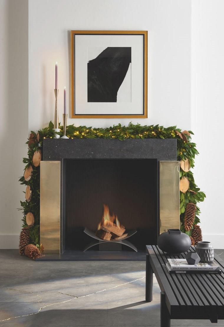 Camino a legna moderno con rivestimento in marmo nero, decorazioni di Natale con ghirlanda e pigne, decora la tua casa