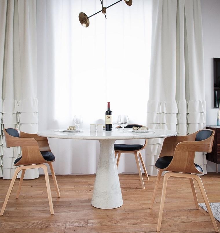 Case moderne interni, sala da pranzo arredata con un tavolo di marmo rotondo e due sedie di legno