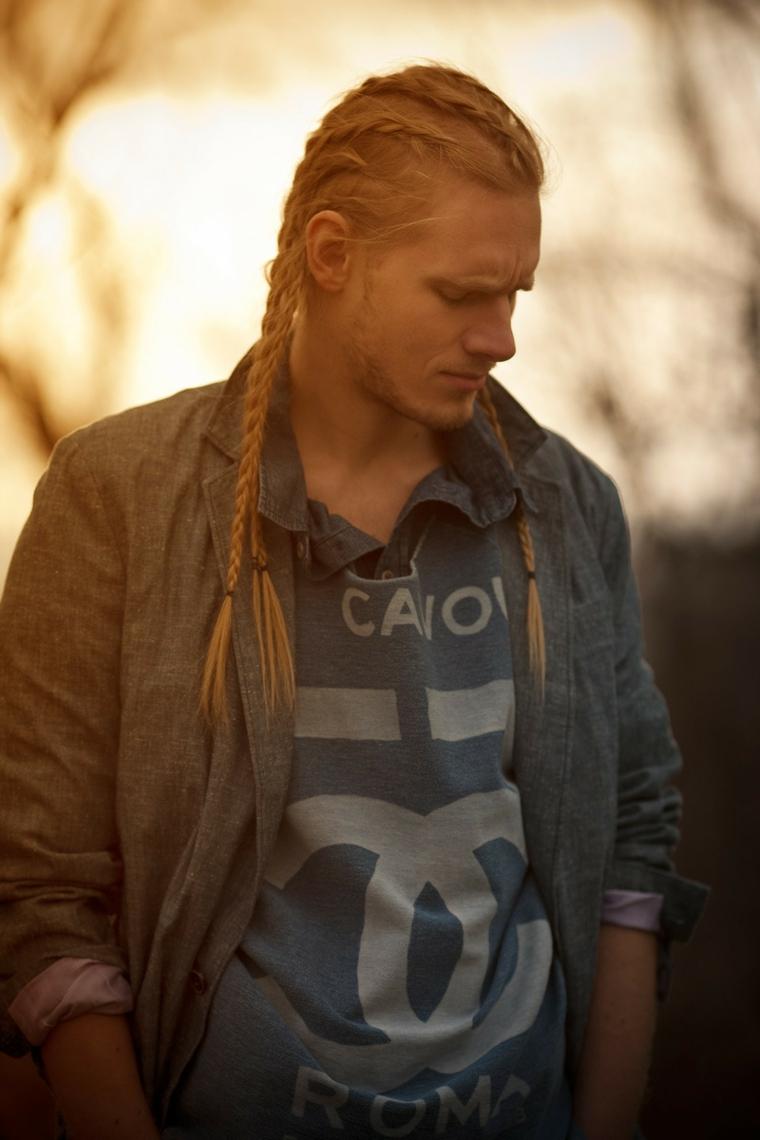 Tagli di capelli uomo colore biondo, trecce legate con elastico, ragazzo vestito in stile casual