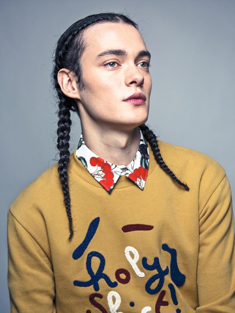 Tagli maschili lunghi, colore nero e acconciatura con trecce, ragazzo con un maglione color senape
