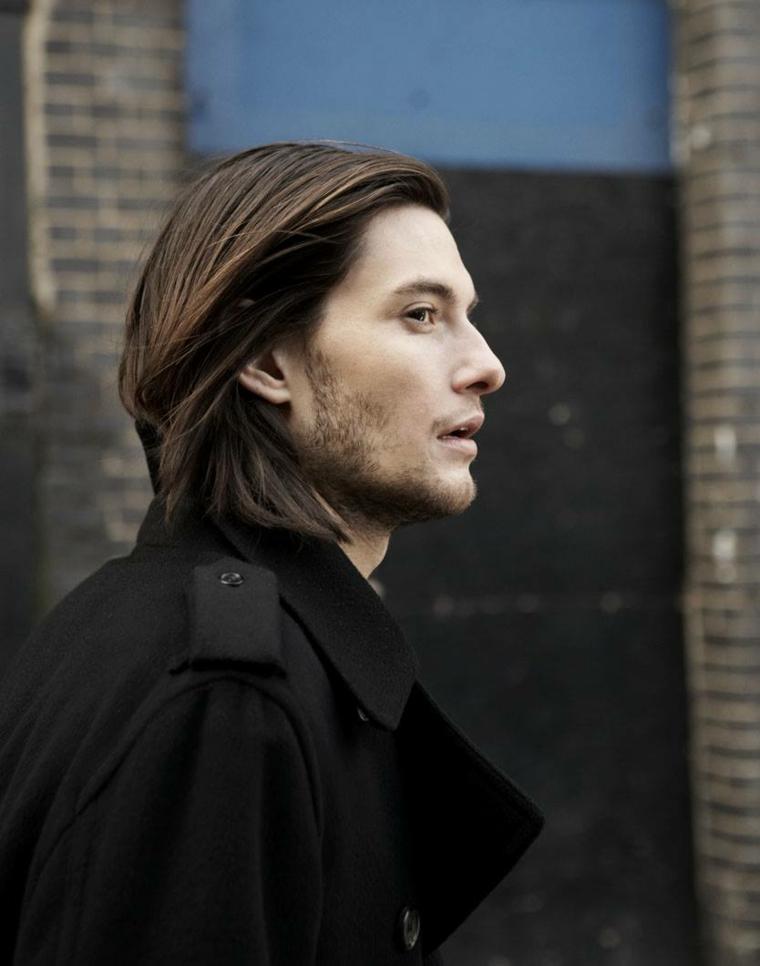 Ragazzo con capelli lunghi a caschetto, colore castano e lisci, stile casual con giacca nera