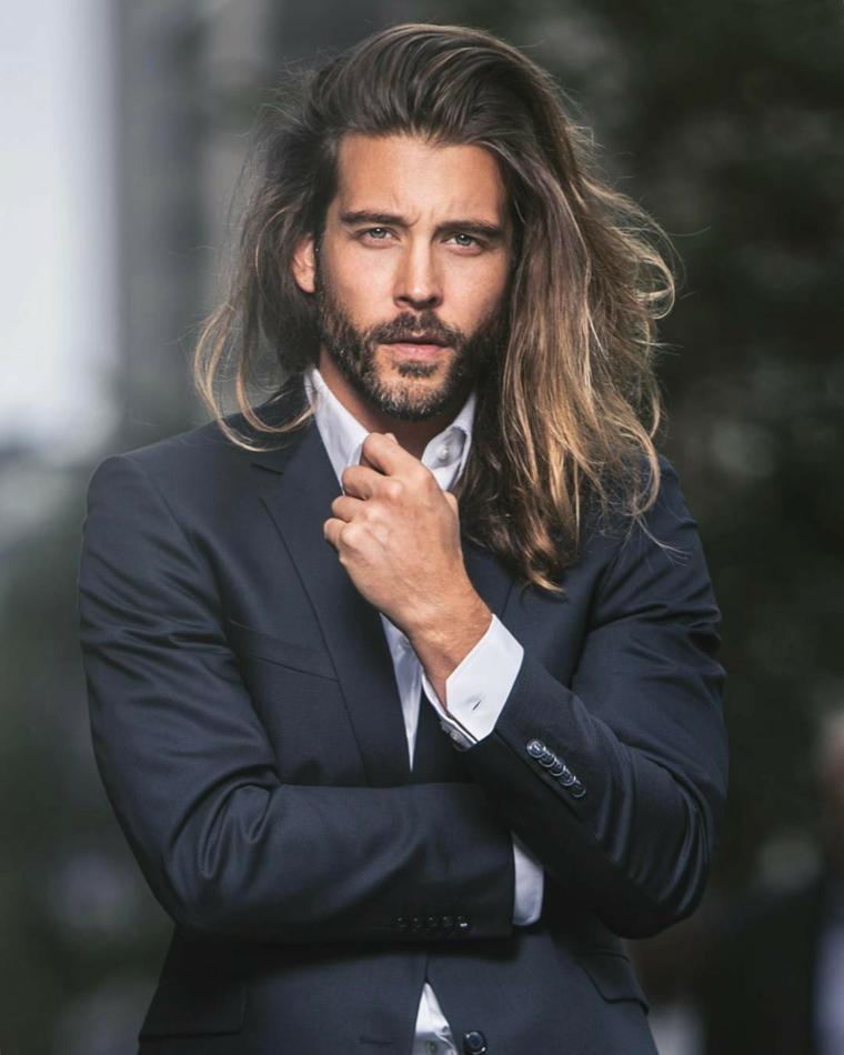 Acconciature uomo con i capelli lunghi, colore castano con colpi di sole biondi, abbigliamento elegante