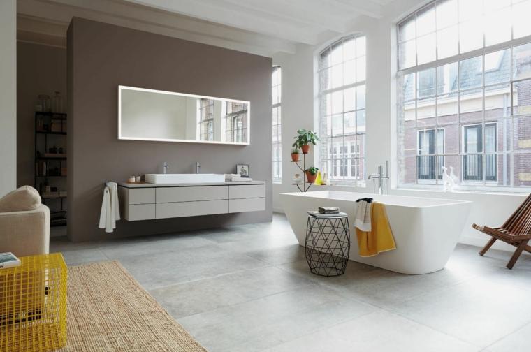 Ambiente molto grande, come arredare un bagno, vasca rettangolare, mobile lungo sospeso, specchio appeso alla parete grigia