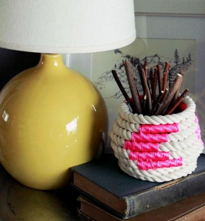 Un cestino di corda di colore bianco, decorazione rosa e bastoncini di legno