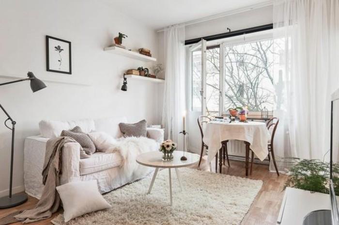 un soggiorno con un divano bianco e cuscini beige, una lampada con piantana. mensole e tavolo in legno