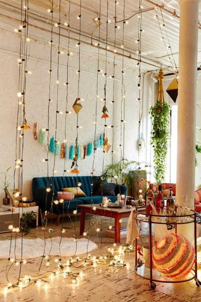 un'idea per ottimizzare lo spazio in case piccole con divano blu, tavolino in legno fili luminosi e piante