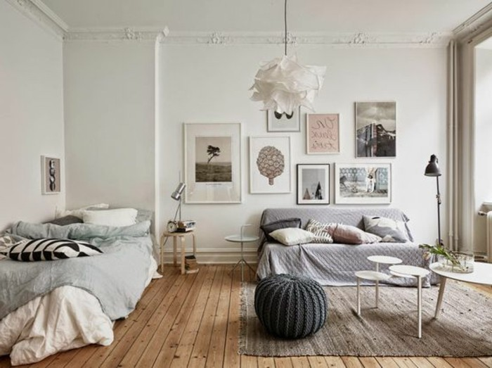 un'idea per arredare monolocale con un divano e un letto a una piazza, tavolino da caffé e sgabello rotondo grigio