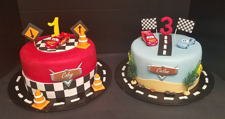 Due torte di compleanno per bambini. forma rotonda rivestite e decorate con i personaggi dell cartone animato Cars
