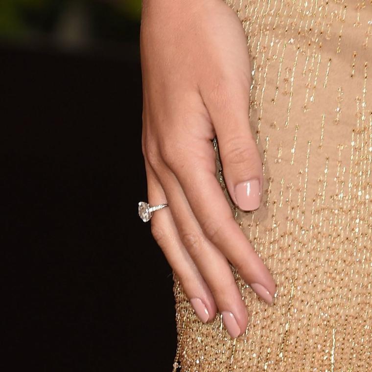 esempio di manicure semplice ed elegante con unghie rosa cipria, anello di brillanti e abito dorato