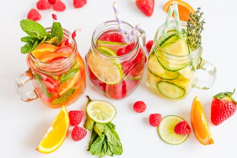 Bevanda sgonfia pancia, barattoli di vetro con acqua e frutta, bere con cannucce colorate