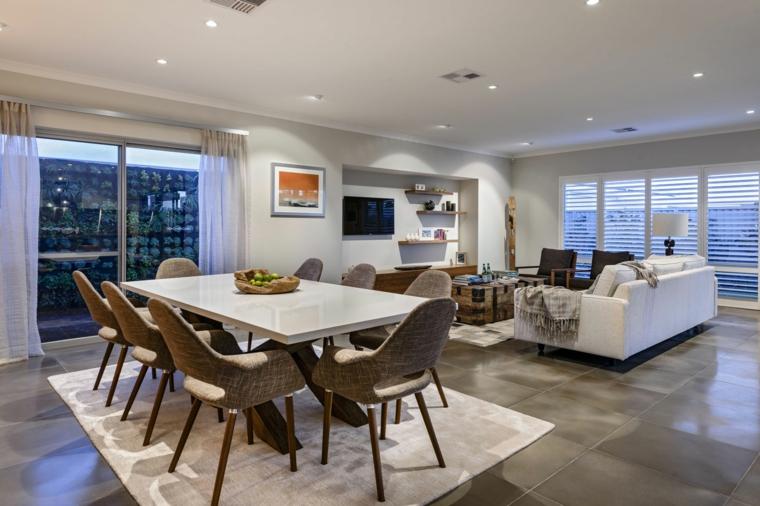 soluzione open space con tavolo da pranzo con top bianco, sedie di design marroni, zona soggiorno con divano bianco