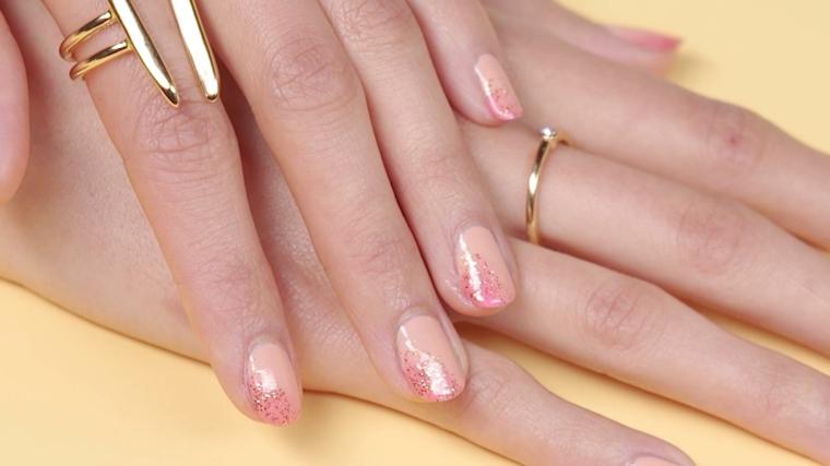 manicure semplice ed elegante con base di smalto nude e brillantini fucsia laterali