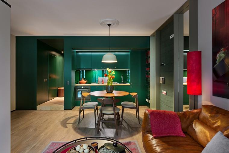 Cucina soggiorno ambiente unico, parete di colore verde, arredamento con set tavolo da pranzo e divano in pelle