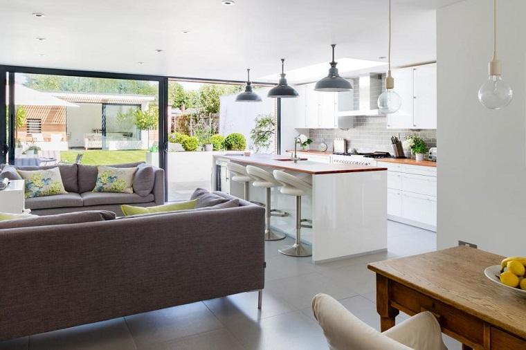Cucina soggiorno open space, pavimento in gres colore grigio, portafinestra molto grande con giardino in vista