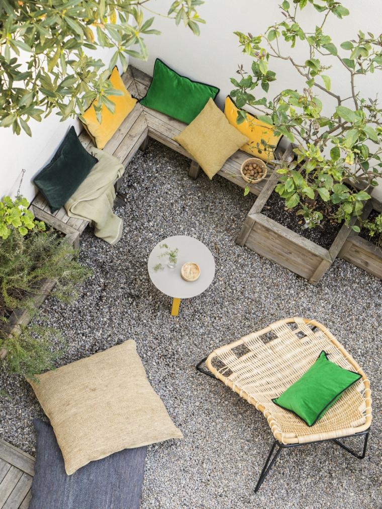 Un piccolo giardino con pavimentazione in ghiaia e panchina in legno con tanti cuscini colorati