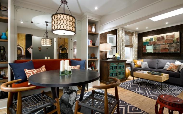 idea per arredare salotto e sala da pranzo insieme in stile indiano con tavolo tondo, tappeti fantasia geometrica e un grande specchio appeso