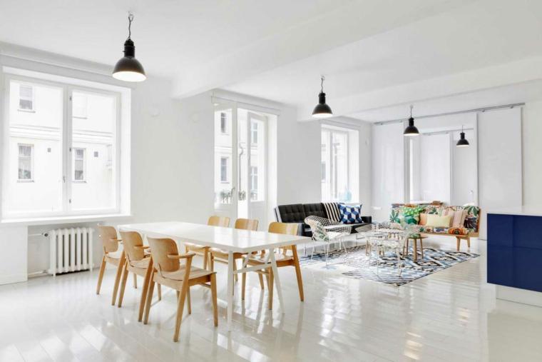 open space arredato in stile scandinavo con pavimento, pareti e tavolo bianchi, divano con cuscini colorati