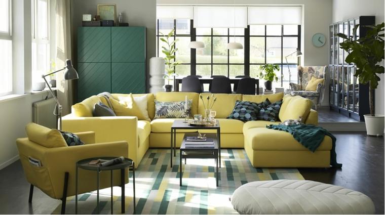 Cucina soggiorno open space, divano a C di colore giallo, tavolini bassi in metallo neri