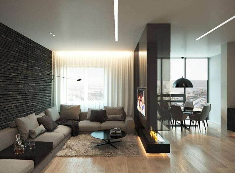 Salotto con parete divisoria, divano grigio angolare, parete con camino moderno