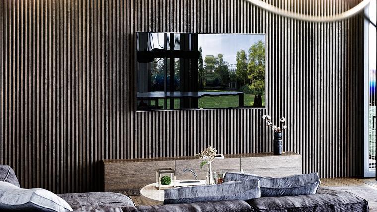 Salotto con parete di legno, tv appesa alla parete, mobile di legno basso