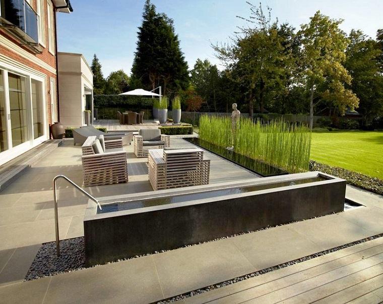 Giardini idee da copiare, pavimento con ghiaia e una piccola fontana, mobili in legno