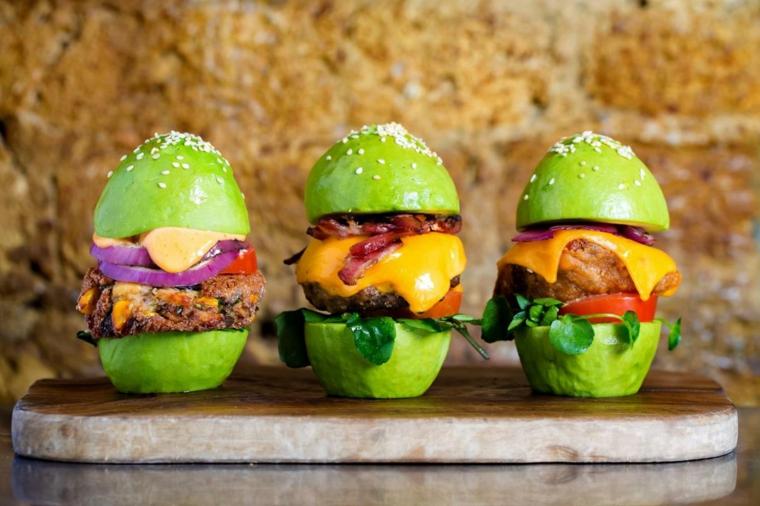 Cosa mangiare a cena, hamburger originali di avocado con pane di colore verde, cipolla rossa e formaggio fuso all'interno