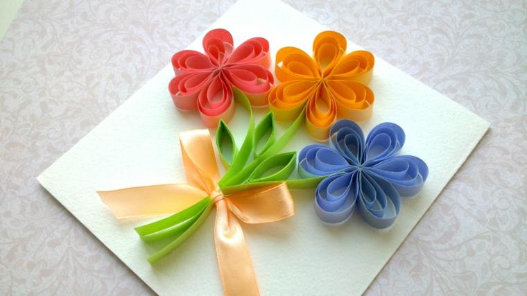 fiori colorati realizzati con la carta blu, giallo e rosso con un fiocco incollati ad un foglio, idea regalo per la festa della mamma