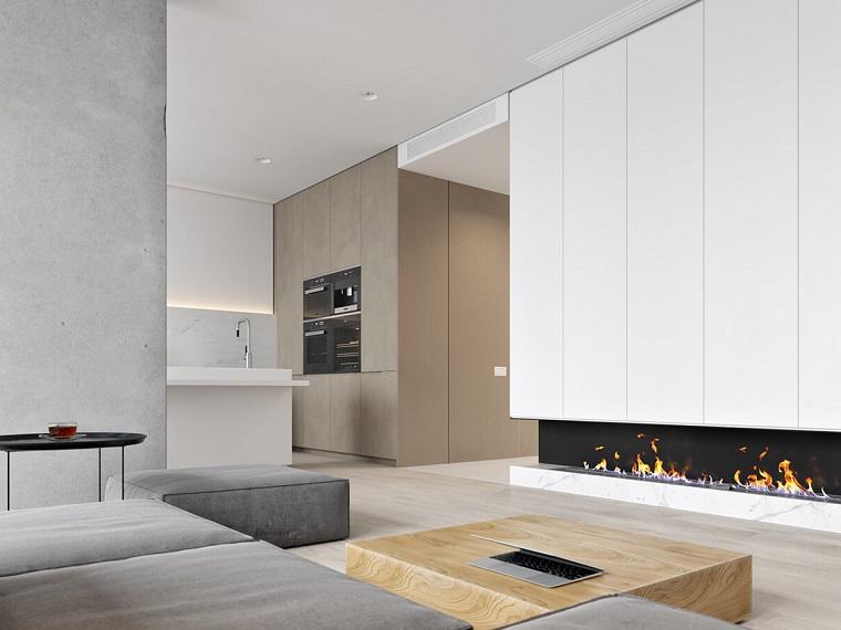 Cucina soggiorno open space, divano di colore grigio e camino moderno, tavolino in legno quadrato, cucina a vista