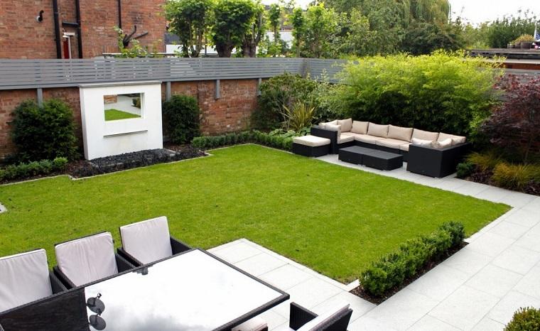 Piccoli giardini di villette, prato verde finto e mobili da esterno in rattan, camino moderno colore bianco