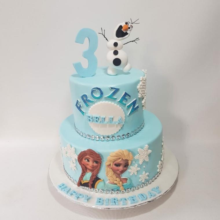 Torta bimba di tre anni con i personaggi di Frozen, a due piani e decorata con fiocchi di neve