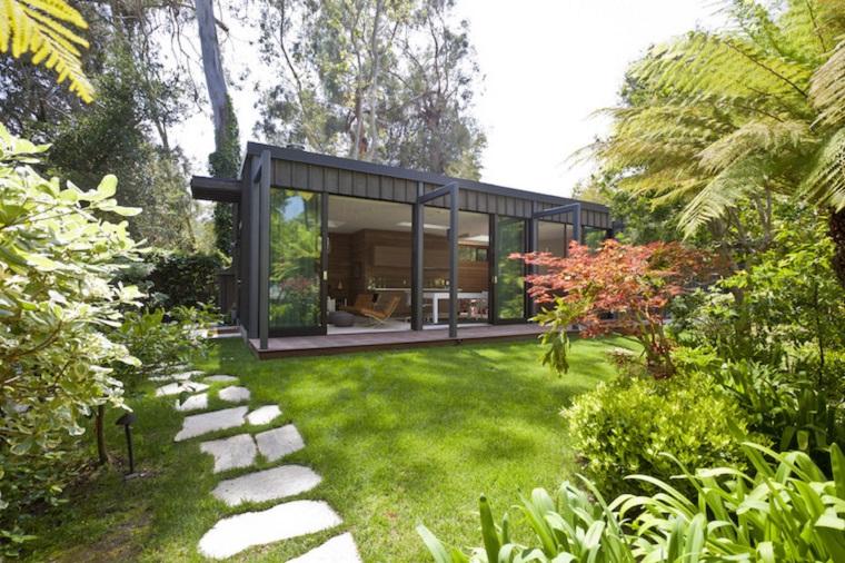 Piccoli giardini di villette, camminamento con pietre e prato verde, casa interamente con vetro