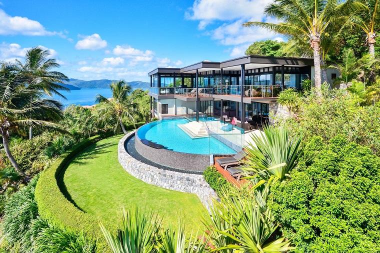 Idee per il giardino con piscina e una siepe bassa, alberi tropicali tipo palme intorno