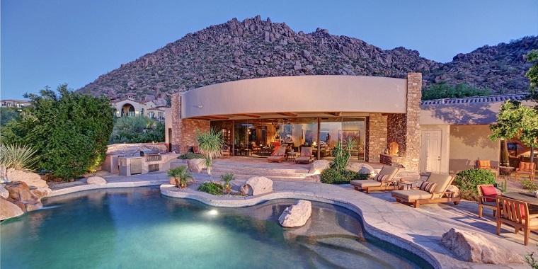 Un giardino bellissimo con grande piscina e pietre grandi come decorazione