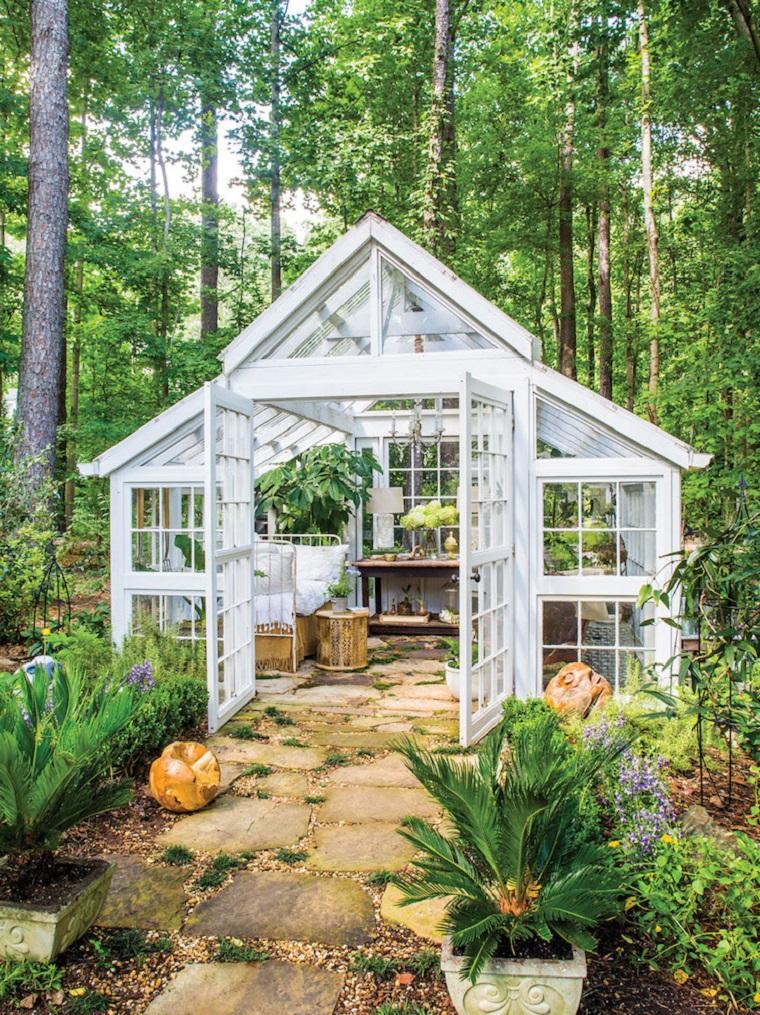 Piccoli giardini di villette, casetta di vetro, camminamento e piante sempreverdi intorno