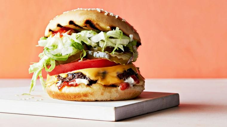 Hamburger con fetta di pomodoro e insalata verde, ricette veloci, formaggio fuso sulla carne