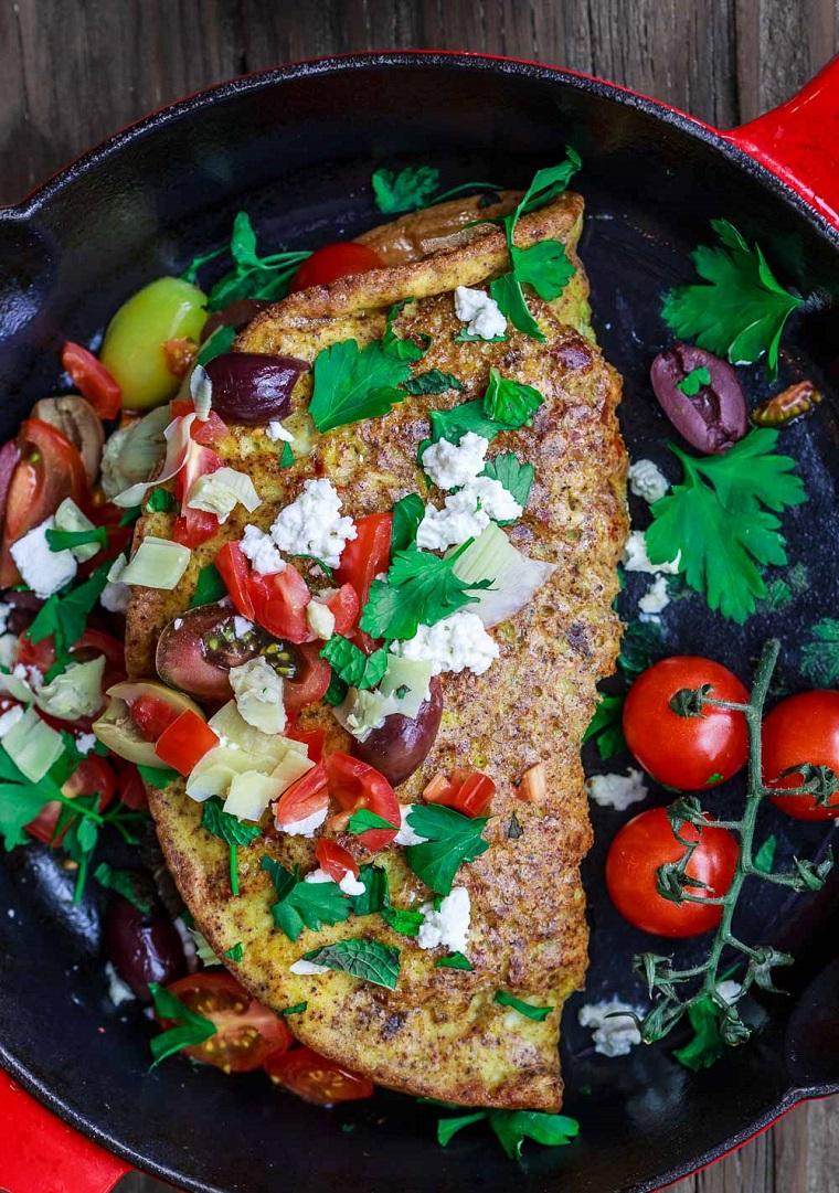 Frittata di uova con contorno di verdure, secondi piatti semplici e gustosi, padella di colore rosso