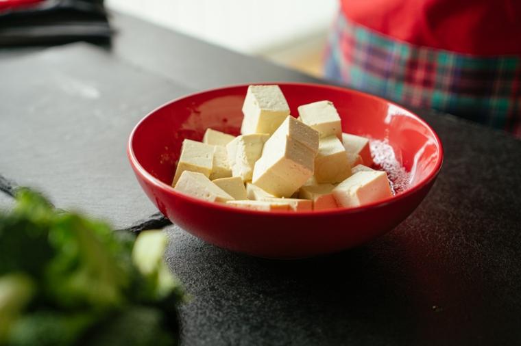 Tofu ricette, piatto di porcellana rossa con cubetti di tofu bianco sgocciolato