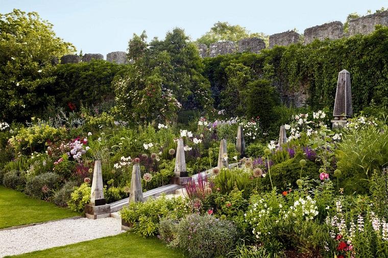 Idee giardino piante e fiori, area esterna in pendenza con un camminamento in ghiaia