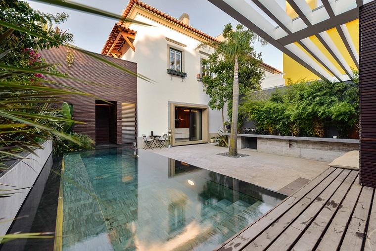 Giardini idee da copiare, piccolo outdoor con piscina e piante tropicali, arredamento con set mobili da esterno