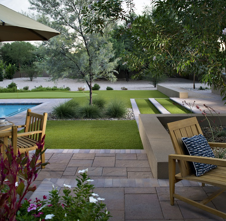 Giardini idee da copiare, prato verde e piscina, mobili di legno con cuscini colorati