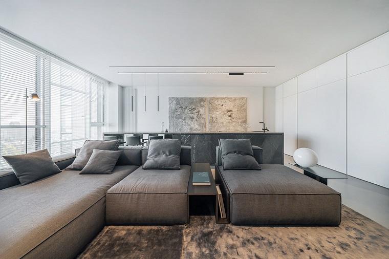 Arredare salotto piccolo, divano di colore grigio, cucina con isola, finestre con tapparelle
